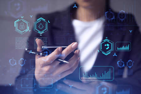 Businesswoman in formal wear holding in the hands a smart phone and testing an innovative application to provide a completely new service. Close up shot. Hologram tech graphs. Concept of Dev team. Stock fotó