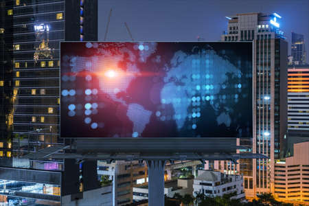 Hologram of Earth planet map on billboard over night panoramic cityscape of Bangkok. The concept of international companies in Southeast Asia.