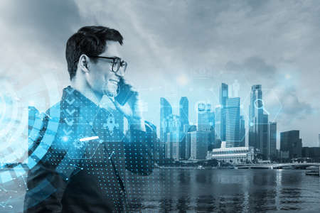 Eastern successful businessman trying to find new ideas using smartphone as a modern tool to solve problems at research and development department. Fintech hologram icons over Singapore. Standard-Bild