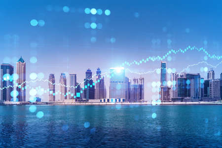 Skyscrapers of Dubai business downtown. International hub of trading and financial services of Western Asia. FOREX graph and chart concept. Double exposure. Dubai Canal waterfront. Stock Photo