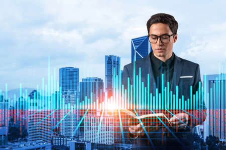 A young eastern handsome trader in suit examine his notes to predict the market behavior based on historic data and stock market. Corporate finance fund and forex chart. Kuala Lumpur. Double exposure