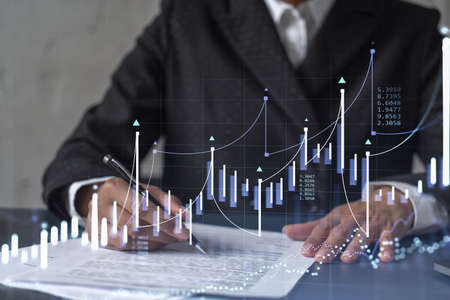 African American businesswoman in formal wear is signing the contract to invest money in stock market. Internet trading and wealth management. Forex and financial hologram chart.
