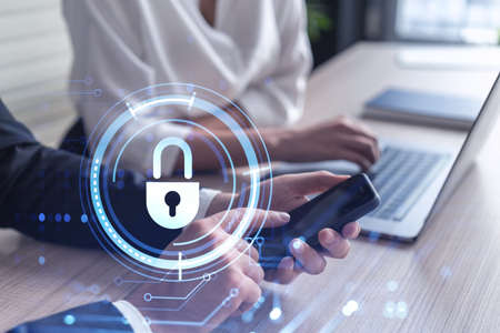 Two businesspeople in formal wear working on the project to protect cyber security of international company using smartphone and laptop. Padlock Hologram icons. Teamwork concept. Stock fotó