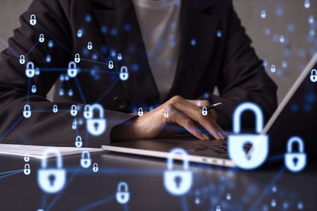 A woman programmer is typing a code on computer to protect a cyber security from hacker attacks and save clients confidential data. Padlock Hologram icons over the typing hands. Formal wear.