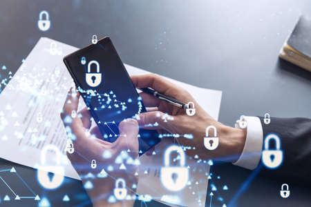A businessman in formal wear reading the contract to prevent probability of risks in cyber security and checking details in the phone. Padlock Hologram icons over the working desk.