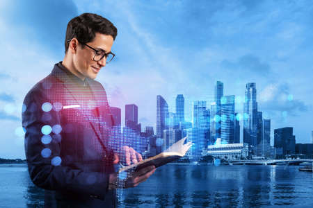 Handsome eastern HR director at international company is looking into personal organizer to plan business meeting to recruit highly qualified specialists. Social media hologram icons over Singapore.