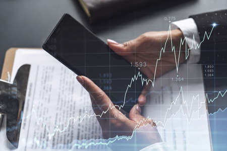 A woman financial trader in formal wear is checking the phone to sign the contract to invest money in stock market. Internet trading and wealth management concept. Forex hologram chart.