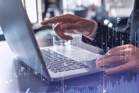 Hands typing the keyboard to research stock market to proceed right investment solutions. Internet trading and wealth management concept. Formal wear. Hologram Forex chart over close up shot. Archivio Fotografico