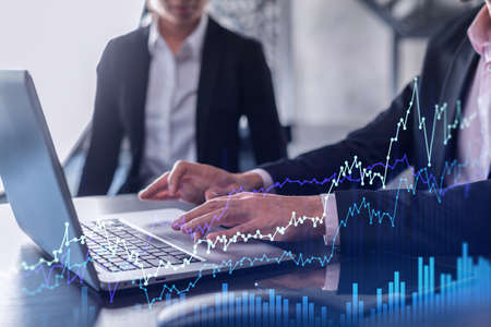 Two traders man and woman researching historic data to predict stock market behavior using laptop. Internet trading concept. Forex and financial hologram chart. Forecasting and planning.