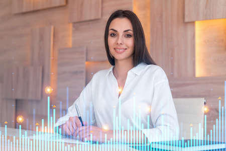 Portrait of attractive businesswoman in formal wear working with documents and thinking how to optimize trading strategy at corporate finance fund. Forex chart hologram over modern office background