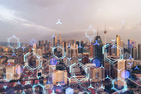 Glowing hologram of technological process, aerial panoramic cityscape of Kuala Lumpur at sunset. KL is the largest innovative hub of tech services in Malaysia, Asia. Multi exposure.
