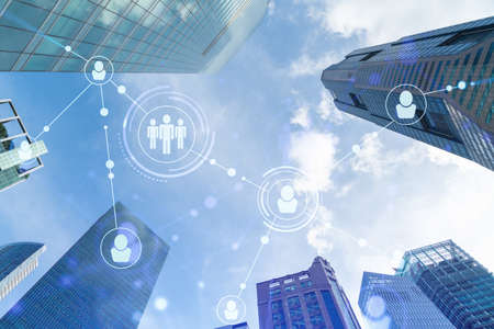Social media icons hologram over low angle shot of Singapore skyscrapers, Southeast Asia. The concept of people networking, connections and career opportunities. Double exposure.
