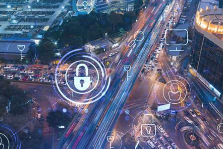 Glowing padlock hologram over night busy road traffic in Bangkok city, Southeast Asia. The concept of cyber security to protect companies. Double exposure.