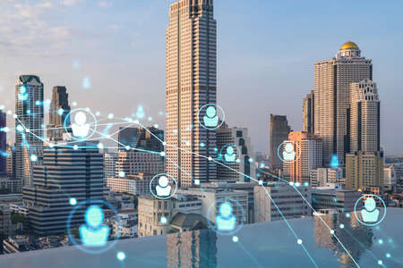 Hologram of social media icons over sunset panoramic cityscape of Bangkok, Southeast Asia. The concept of people connections and career opportunities. Multi exposure.