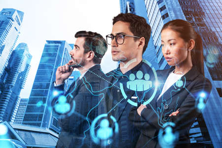Group of SMM specialists working on social media marketing strategy to achieve business goals. Hologram icons over Singapore background. Stock fotó