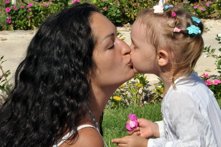A woman with long black curly hair kisses her daughter on a sunny day.