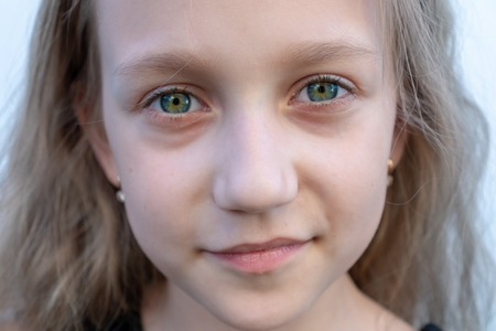 Close-up summer portrait of young girl. 8 years old kid smiling,  blue green eyes. 免版税图像