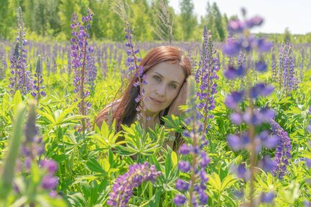 Portrait of a beautiful woman with green eyes brown long hair on a field of flowers.