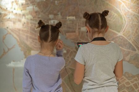 Girls in museum listening to interesting information about exhibit through headphones.