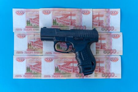 Close up image of pistol and rubles money.
