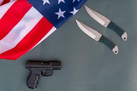 Lanzar cuchillos, pistola, bandera americana plana yacía sobre fondo gris. Leyes de armas de Estados Unidos - Armas y armas