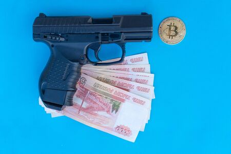 close up image of pistol, Bitcoin coins and rubles moneyon a blue background. Reklamní fotografie