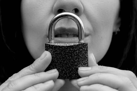 Conceptual portrait of a woman keeping silence with lock over her mouth. caucasian woman keep mouth locked. Language barrier concept and protecting the rights of women. Black and white. Reklamní fotografie - 129085952
