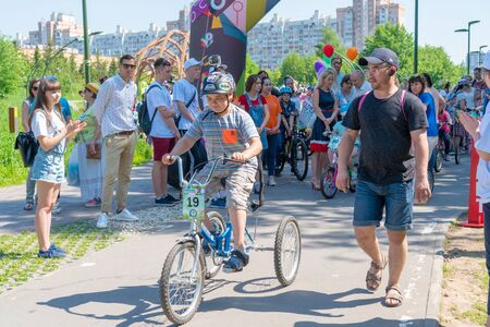 Russia, Kazan - May 31, 2019: A boy with Down Syndrome on a bicycle participates in a cycling race with his father on a sunny summer day. Charity bike ride. Admission is free