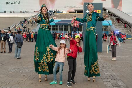 Russia, Kazan - August 27, 2019: Two charming girls on the background of animators in the national Tatar costume on World Skills 2019