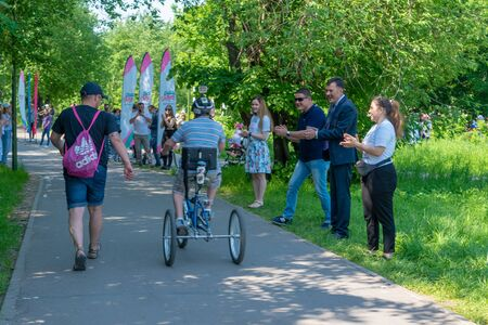 Russia, Kazan - May 31, 2019: A boy with Down Syndrome on a bicycle participates in a cycling race with his father on a sunny summer day