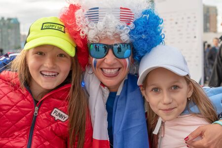 Russia, Kazan - August 27, 2019: close-up Portrait of a smiling fans: Two adorable Russian white kid girls and woman with a painted face in the colors of the Russian flag in the fan zone during the World Skills 2019 China Russia - Image. Russian patriotic