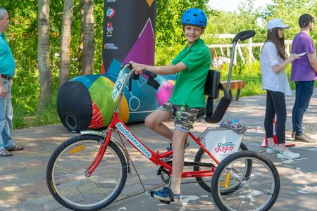 Russia, Kazan - May 31, 2019: Disabled boy in glasses on a tricycle on a bright sunny day. Charity bike ride. Admission is free