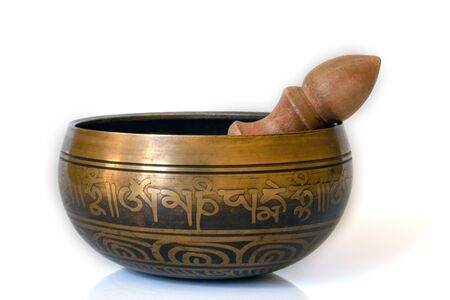 Singing bowl close-up, soothing and meditative. Singing bowl with sanskrit engraving pattern and wooden mallet Isolated on white background.