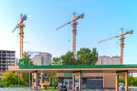 Russia, Kazan - July 7, 2019: three Construction cranes and building under construction against blue sky. three Industrial Crane operating and lifting an concrete block against blue sky. Nearby is a gas station for cars.