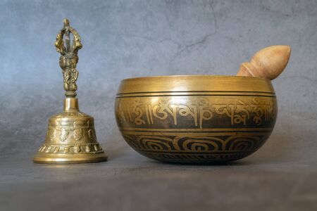Singing bowl and golden bell close-up, soothing and meditative. Singing bowl with sanskrit engraving pattern and wooden mallet and golden bell of on gray background. Symbols of Asia