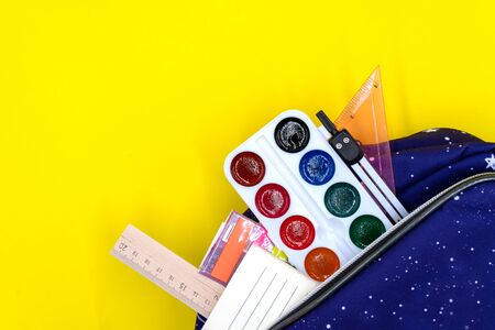 Colorful school supplies in a school backpack on a yellow background, back to school concept. Sale of school supplies and stationery. Space for text