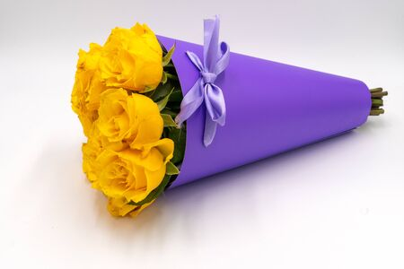 A bouquet of yellow roses in a stylish and modern package in the shape of a cone with handles on a white background. Mothers day and birthday. Stock Photo