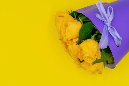 A bouquet of yellow roses in a stylish and modern package in the shape of a cone on a yellow background. Mothers day and birthday.