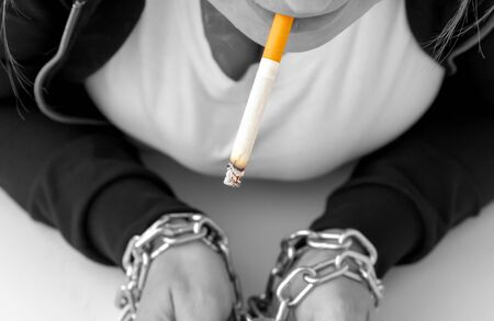 Womans hands tied by chain with cigarette on a white background. Stop smoking concept, cigarettes, A woman with red hair smokes a cigarette, hands tied with a chain. black and white. Stock fotó