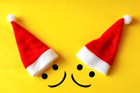 Two merry christmas smiles in santa claus hats on yellow background. Friendship and love