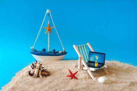 Sonys miniature laptop on a miniature blue deck chair. Freelance Part time Outsources Job Employment Concept. Work on travel. Russia, Tatarstan, September 05, 2019 Redakční