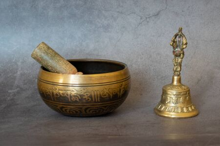 Singing bowl and golden bell close-up, soothing and meditative. Singing bowl with sanskrit engraving pattern and wooden mallet and golden bell of on gray background Stok Fotoğraf