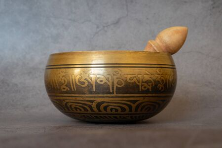 Singing bowl close-up, soothing and meditative. Singing bowl with sanskrit engraving pattern and wooden mallet Isolated on gray background. Symbols of Asia. Stok Fotoğraf