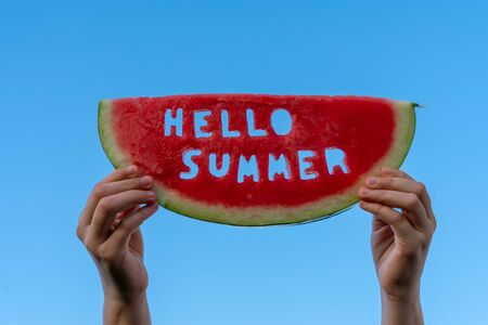 A piece of watermelon against a blue sky. Childrens hands are holding a slice of watermelon with the text Hello Summer. Summer time concept Stockfoto
