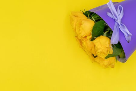 A bouquet of yellow roses in a stylish and modern package in the shape of a cone on a yellow background. Mothers day and birthday