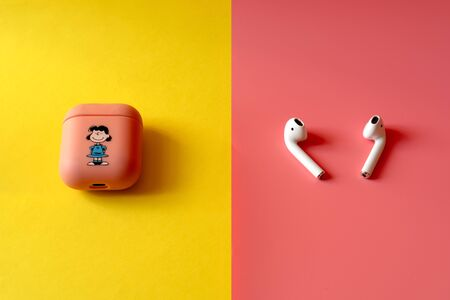Apple AirPods wireless headphone with charging box on a multi-colored background pink and yellow . Use with Iphone, Ipad or Mac . Apple AirPods charging box in a fun and vibrant pink case. Protect your headphones and charger in a case. Russia, Tatarstan,