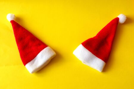 Two red santa claus hats on a yellow background. Couple in love. The concept of love and the New Year and Christmas