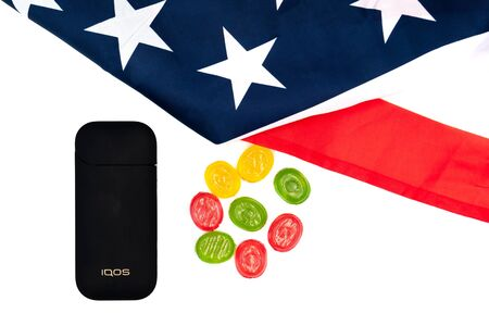 Black IQOS Box, Americas Flag and multicolored sweet candy lollipops on white background. Iqos electronic cigarette ban concept in the USA. The dependence of adolescents on electronic cigarettes with sweet taste. Russia, Tatarstan, September 08, 2019