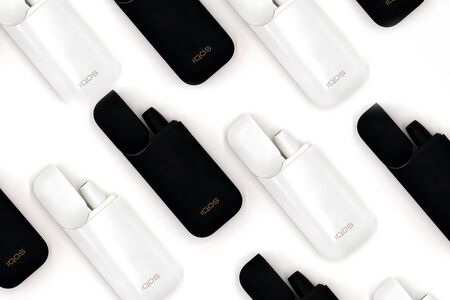 White Iqos device battery and black Iqos device battery isolated on white background. Lots of Iqos. Russia, Tatarstan, September 08, 2019