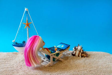 Miniature people girl with pink hair sits in a deck chair with a laptop and a glass of drink in her hands and looks at the sea. Freelance Part time Outsources Job Employment Concept. Russia, Tatarstan, September 05, 2019.